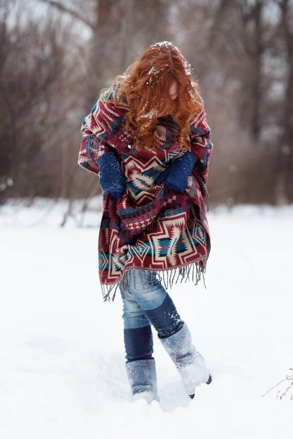 Jeune femme rousse dans la forêt d'hiver elle est habillée dans une écharpe ethnique images stock