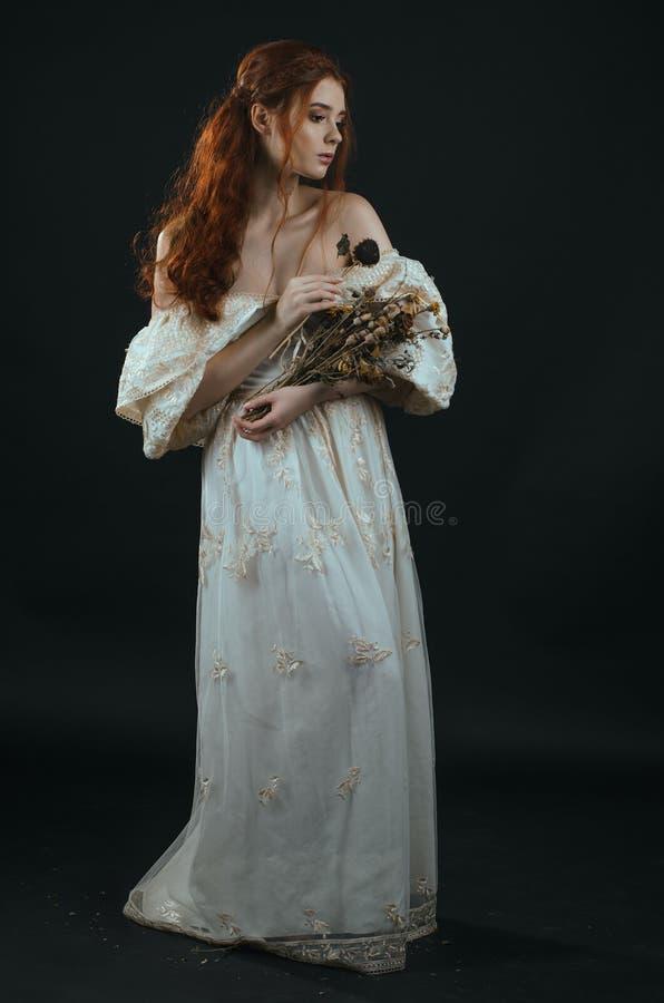 Jeune femme rousse dans une robe d'or de vintage avec les épaules nues avec un bouquet sec dans des mains sur un fond noir dans l images stock