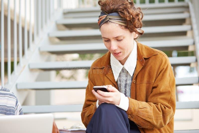 Jeune femme rousse de hippie à l'aide du smartphone photos stock