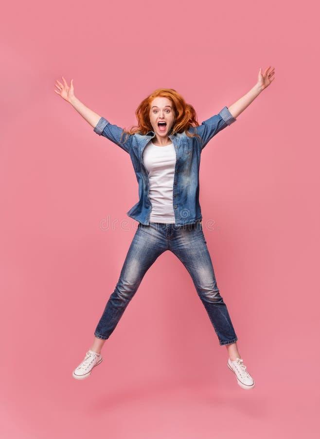 Jeune femme rousse de sourire sautant en air image stock