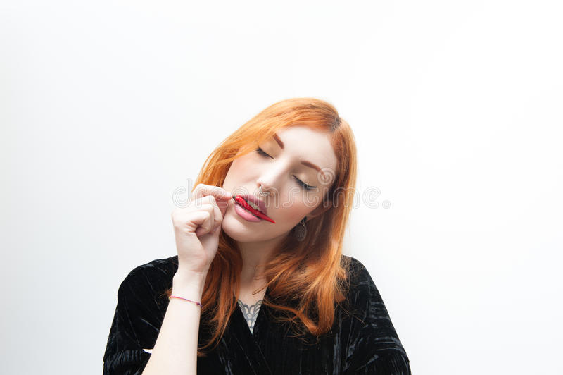 Jeune femme rousse goûtant le poivre de piment d'un rouge ardent image stock
