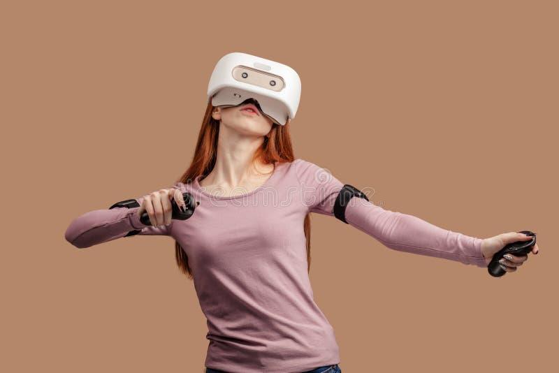 Jeune femme rousse heureuse ? l'aide d'un casque de r?alit? virtuelle image libre de droits