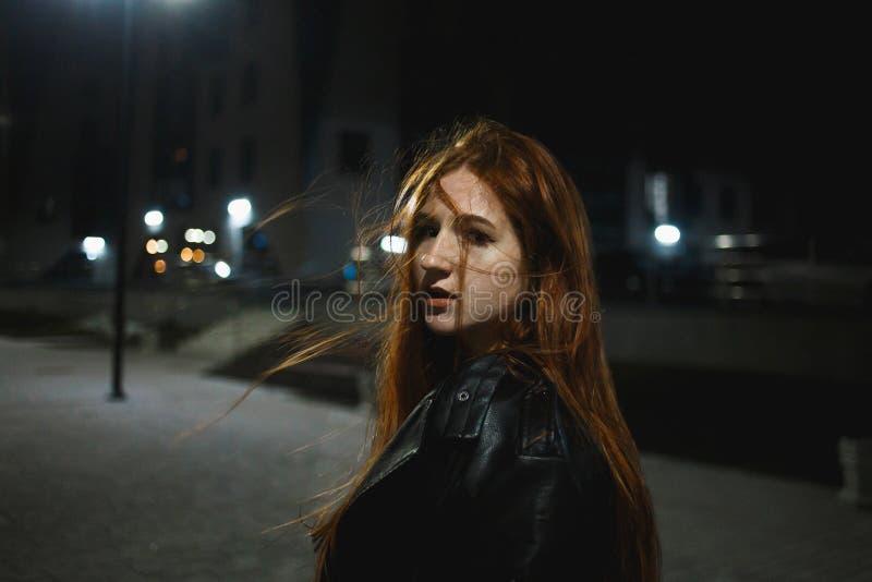 Jeune femme rousse ?l?gante posant dans la ville de nuit image stock