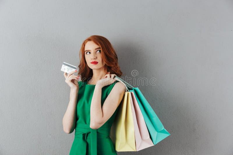 Jeune femme rousse réfléchie tenant des paniers photographie stock libre de droits