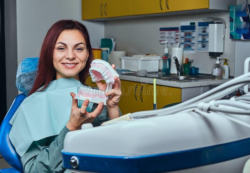 Jeune femme rousse s'asseyant dans une chaise de dentiste et tenant le dentier dans un bureau de dentiste photo stock