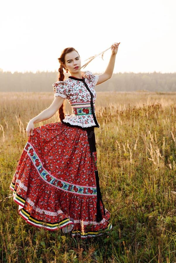 Jeune femme rurale, habillée dans le costume national hongrois, posant au-dessus du fond de nature photo libre de droits