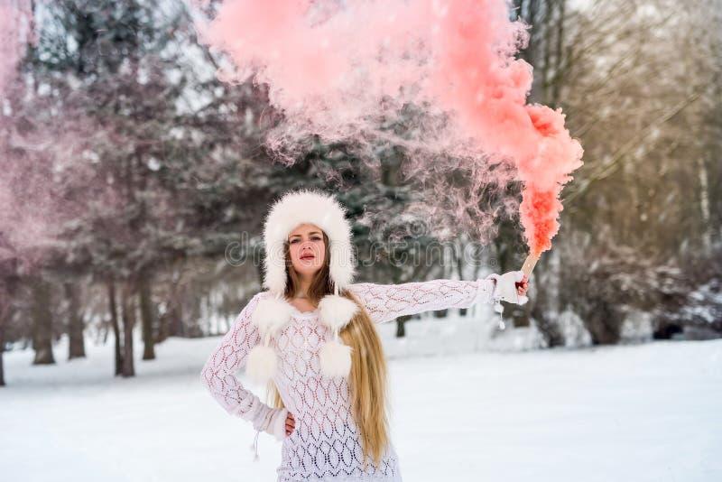 Jeune femme séduisante avec une bombe à fumées rouges image stock