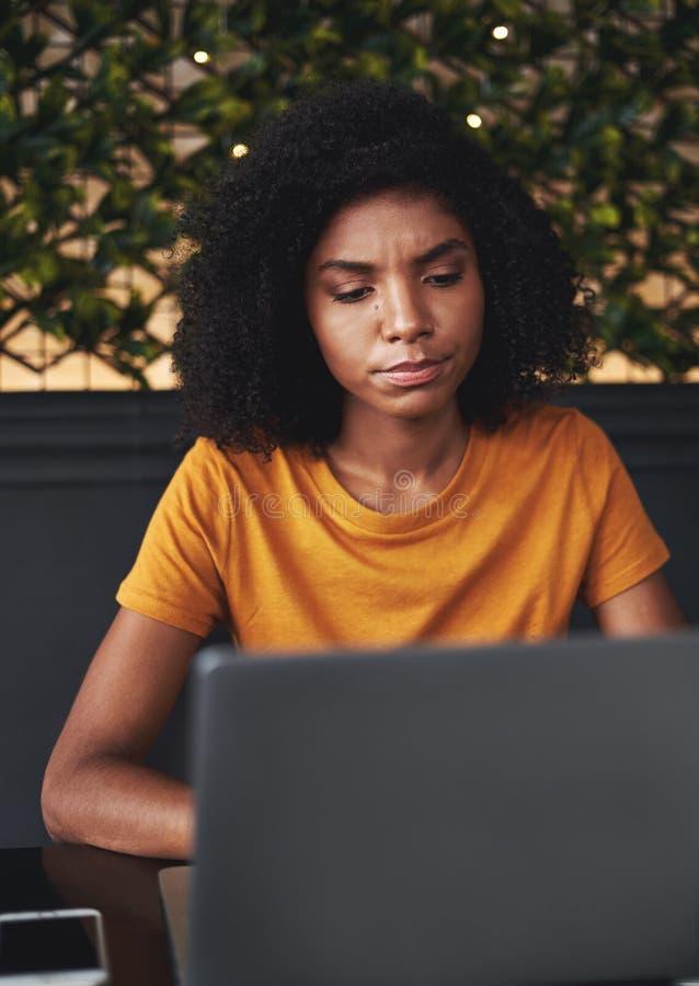 Jeune femme sérieuse à l'aide de l'ordinateur portable en café image stock