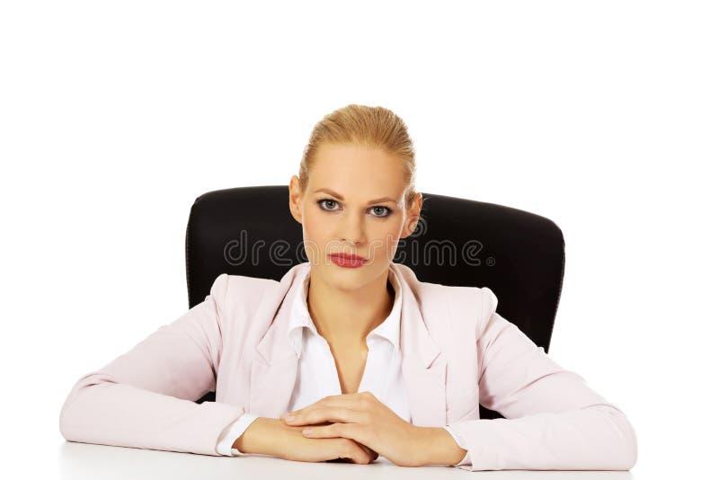 Jeune femme sérieuse d'affaires s'asseyant derrière le bureau image libre de droits
