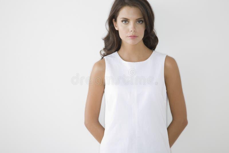 Jeune femme sérieuse dans la robe blanche photographie stock libre de droits