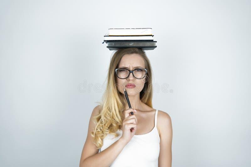 Jeune femme sérieuse dans le stylo de participation en verre dans sa main et livres sur son fond blanc principal image libre de droits