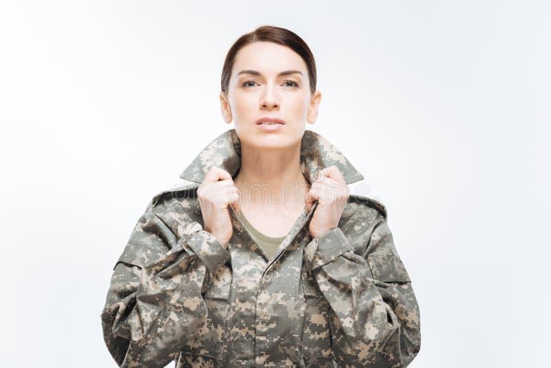 Jeune femme sérieuse plaçant son collier photos libres de droits