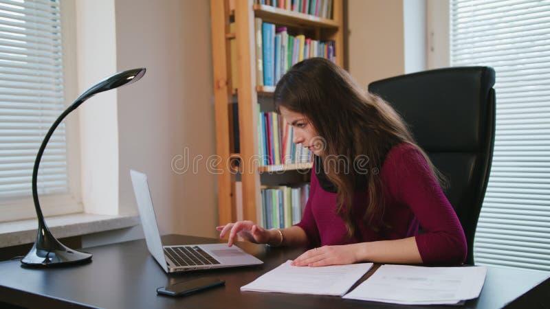 Jeune femme sérieuse regardant sur des documents photo stock