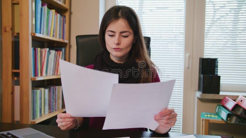 Jeune femme sérieuse regardant sur des documents photographie stock libre de droits