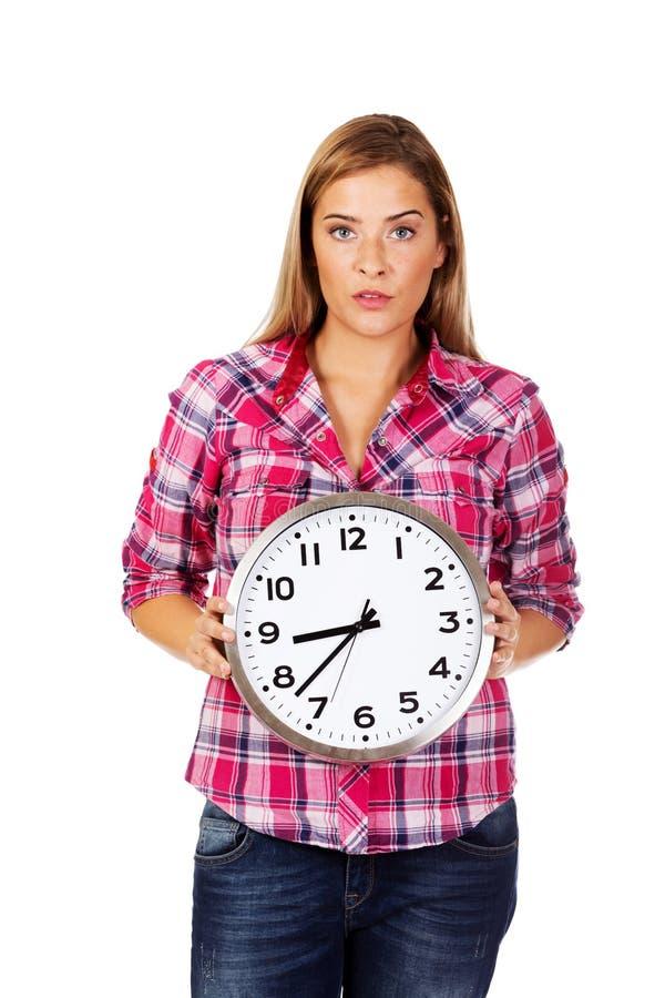Jeune femme sérieuse tenant l'horloge photos libres de droits