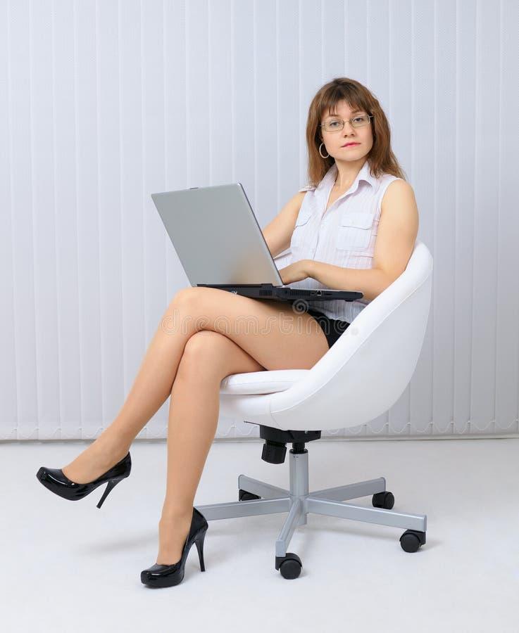 Jeune femme sérieux et beau s'asseyant dans une présidence photos stock