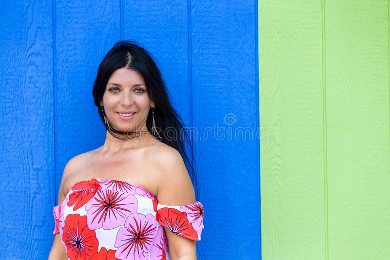 Jeune femme sûre de sourire contre le bois bleu images stock
