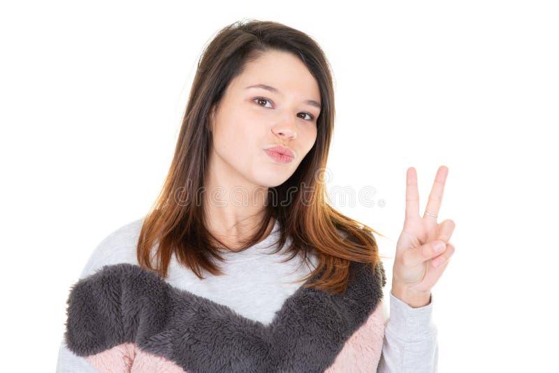 Jeune femme sûre heureuse de portrait donnant le geste de signe de la victoire deux de paix et le fond blanc de studio d'isoleme images stock