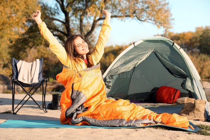Jeune femme s'étirant dans le sac de couchage près de la tente de camping photos libres de droits