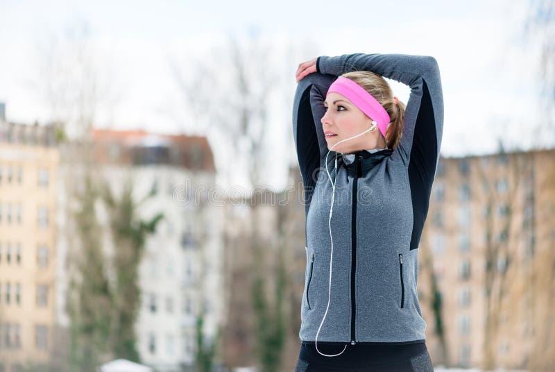 Jeune femme s'étirant pendant la formation de sport extérieure image stock