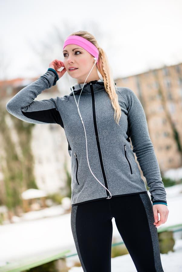 Jeune femme s'étirant pendant la formation de sport extérieure un hiver image stock