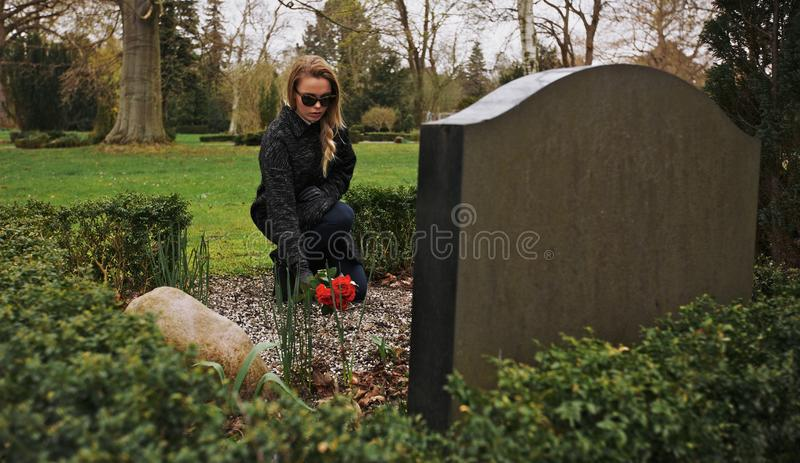 Jeune femme s'affligeant au cimetière photos stock