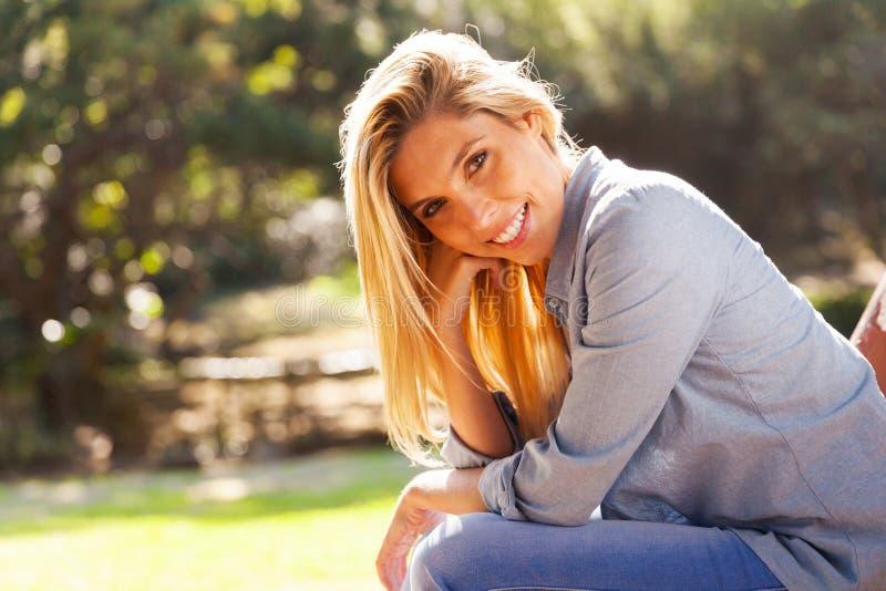 Jeune femme s'asseyant à l'extérieur image stock