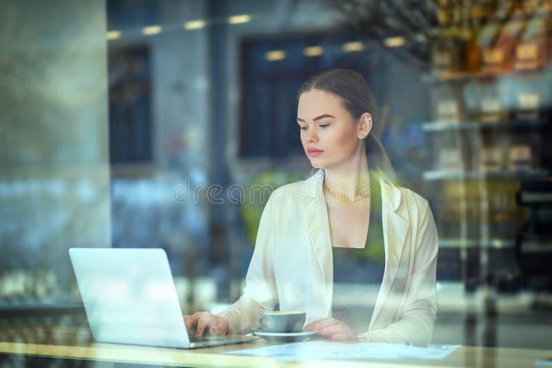 Jeune femme s'asseyant à la table de fenêtre en café potable de cafétéria et travaillant sur l'ordinateur portable image stock