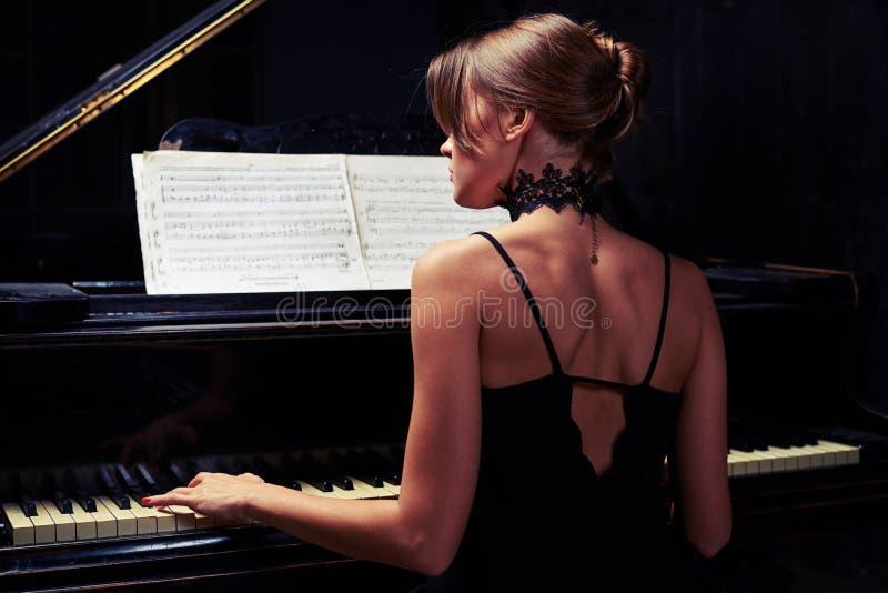 Jeune femme s'asseyant au piano dans la robe nue de dos de noir photo stock