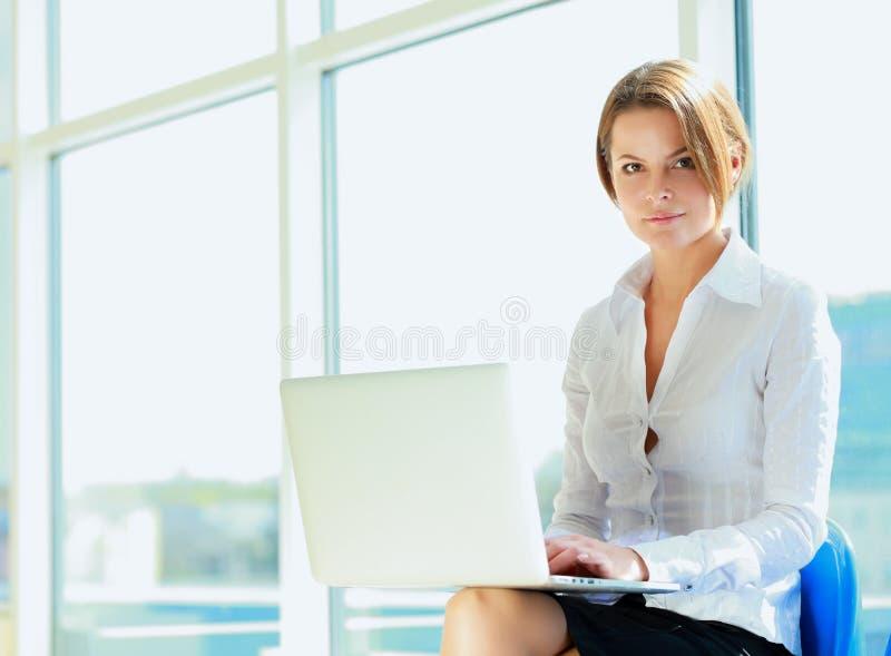 Jeune femme s'asseyant avec l'ordinateur portable photos stock