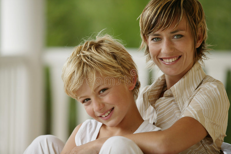 Jeune femme s'asseyant avec un garçon à l'extérieur photographie stock libre de droits