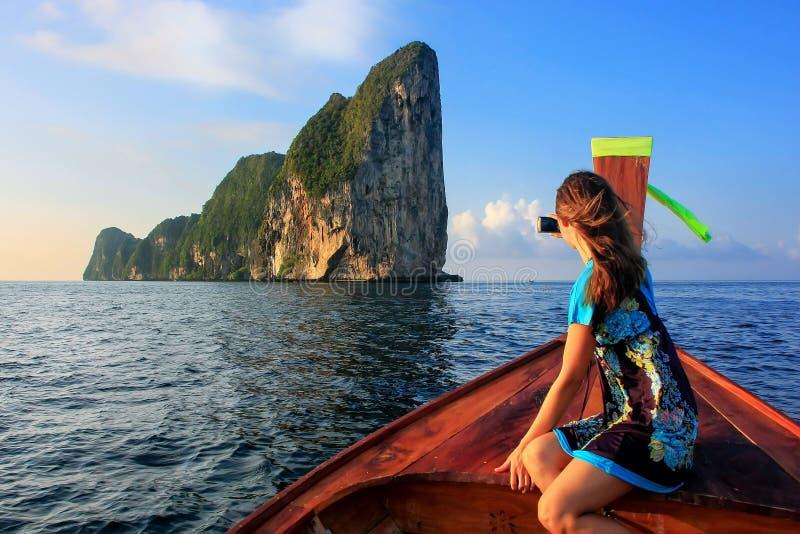 Jeune femme s'asseyant dans l'avant d'un bateau de longtail allant au phi photo stock