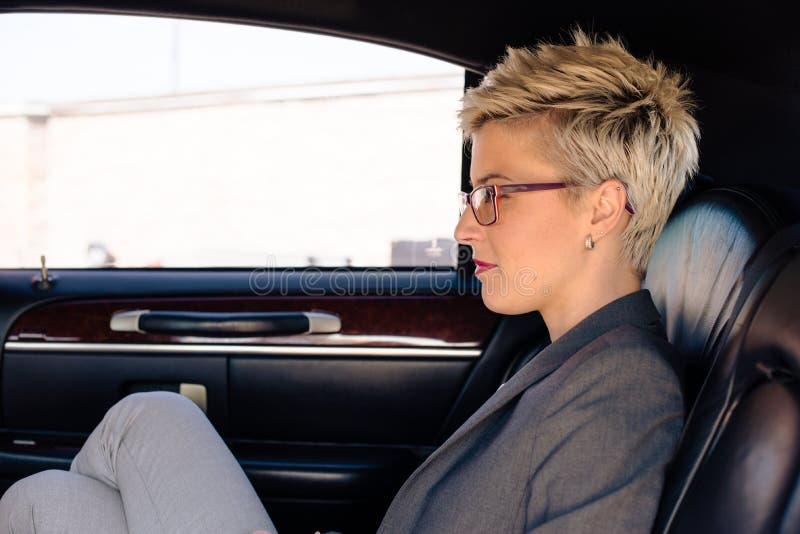 Jeune femme s'asseyant dans la limousine photo stock
