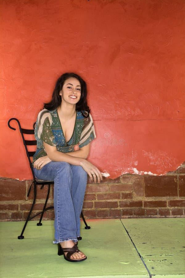 Jeune femme s'asseyant dans la présidence photo stock