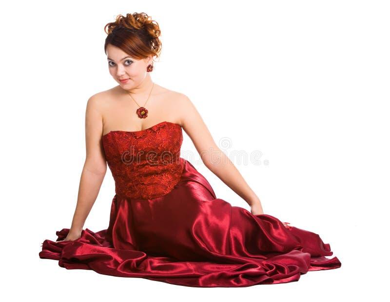 Jeune femme s'asseyant dans la robe rouge. photos stock