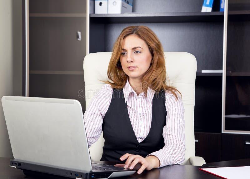jeune femme s 39 asseyant dans le bureau dactylographiant sur l 39 ordinateur portable photo stock. Black Bedroom Furniture Sets. Home Design Ideas