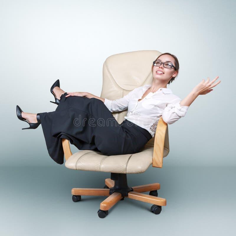 Jeune femme s'asseyant dans le fauteuil images stock