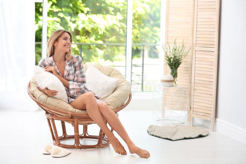Jeune femme s'asseyant dans le fauteuil confortable photo libre de droits