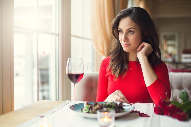Jeune femme s'asseyant dans le restaurant dinant regardant la fenêtre photo stock