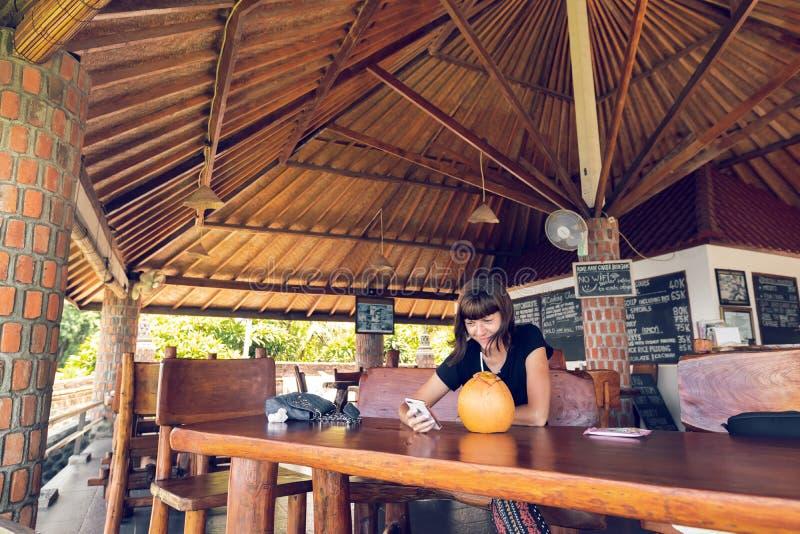 Jeune femme s'asseyant dans un café tropical avec la noix de coco Île de Bali images libres de droits