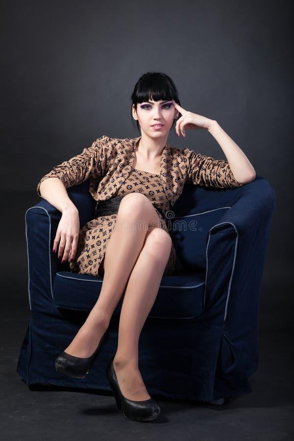Jeune femme s'asseyant dans un fauteuil de marine photographie stock libre de droits