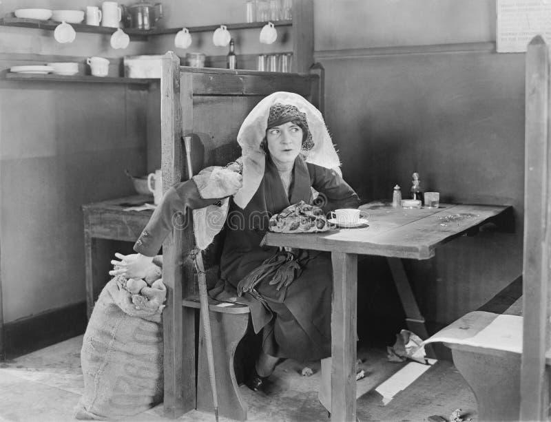 Jeune femme s'asseyant dans une cabine dans un wagon-restaurant, essayant de voler quelque chose hors d'un sac de jute (toutes le photographie stock