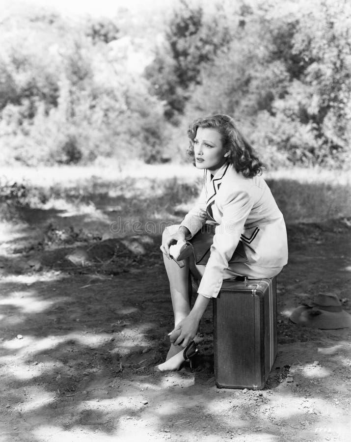 Jeune femme s'asseyant du côté de la route sur sa valise, la frottant pieds douloureux (toutes les personnes représentées ne sont images stock