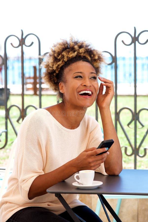 Jeune femme s'asseyant en café avec le téléphone portable et rire photos libres de droits