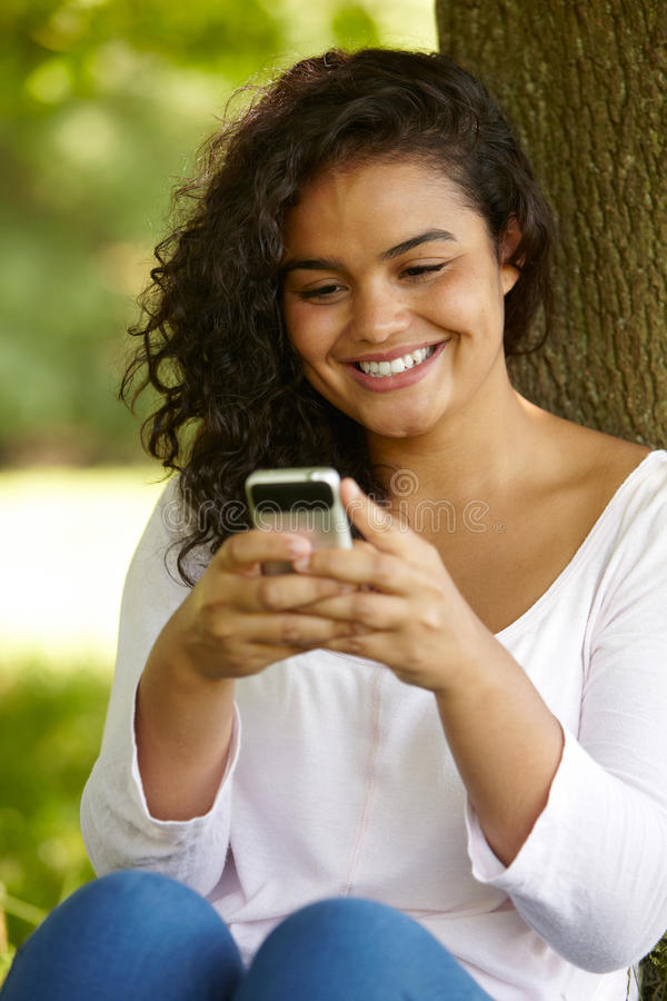 Jeune femme s'asseyant en parc envoyant le message textuel photos libres de droits