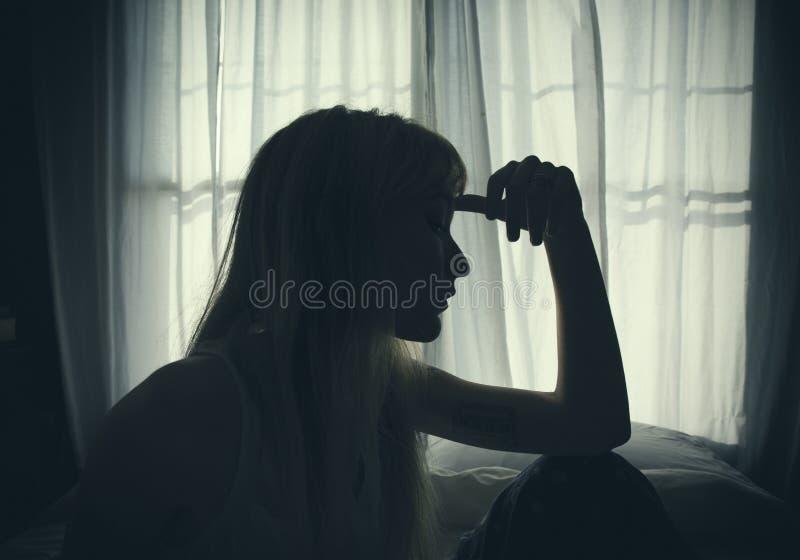 Jeune femme s'asseyant par une fenêtre sur un lit photo libre de droits