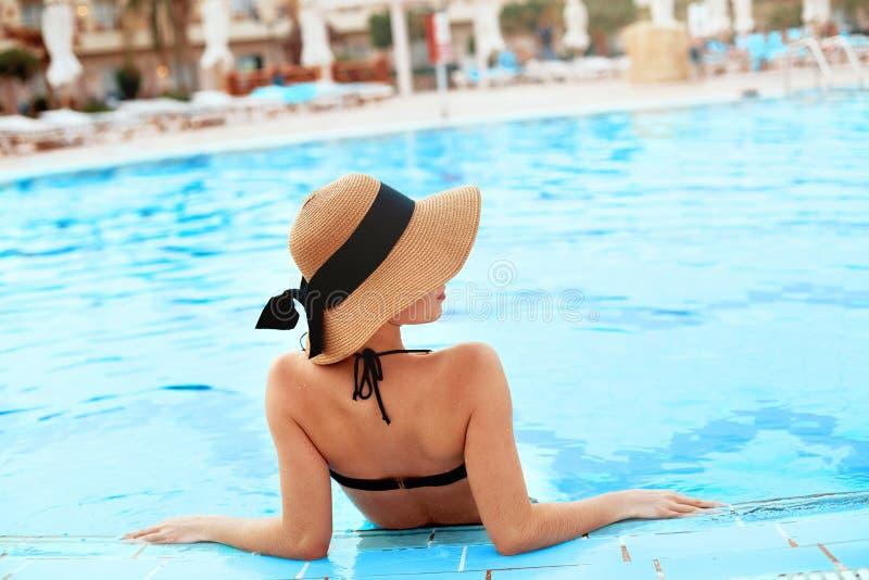 Jeune femme s'asseyant près de la piscine Fille sexy avec la peau bronzée saine Femelle avec le chapeau du soleil détendant da images libres de droits