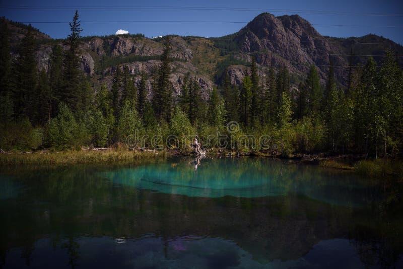 Jeune femme s'asseyant près du lac bleu de montagne photographie stock