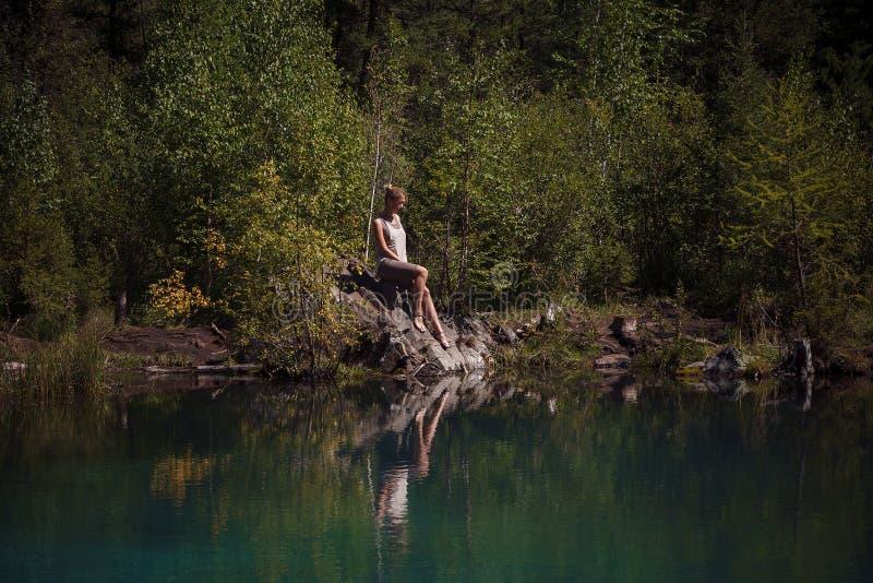 Jeune femme s'asseyant près du lac bleu de montagne image stock