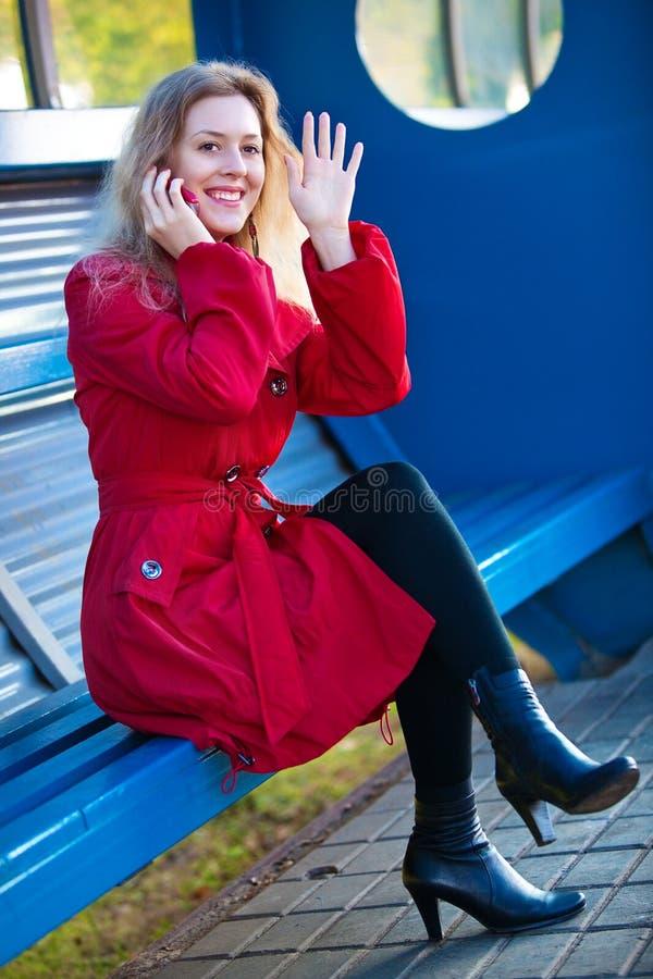 Jeune femme s'asseyant sur l'arrêt de gare photo stock
